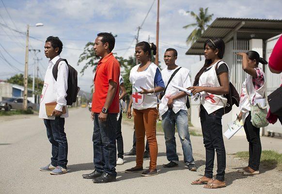 Volunteers from Cruz Vermelha Timor Leste's Dili branch visits a home as part of a dengue outreach education program.