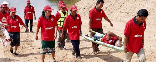 Khammouane Province, Laos, 2015 Transporting the patient. Participants practice transporting a patient during a Community Based Disaster Risk Reduction simulation. The exercises and drills focus on disaster preparedness and response at village level, ensuring communities are equipped with skills to activate emergency plans and save lives. Through the simulation project Lao Red Cross and partner French Red Cross, with support from the European Union, are improving safety for vulnerable communities.