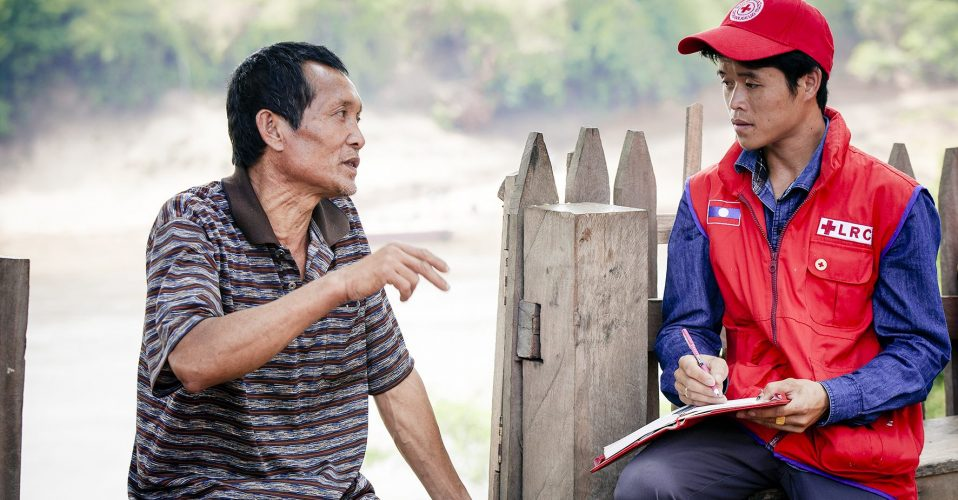 Khammouane Province, Laos, 2015 Lao Red Cross staff interview father and farmer Hong, 47, about his experience with floods during a Community Based Disaster Risk Reduction simulation. The exercises and drills focus on disaster preparedness and response at village level, ensuring communities are equipped with skills to activate emergency plans and save lives. Through the simulation project Lao Red Cross and partner French Red Cross, with support from the European Union, are improving safety for vulnerable communities.