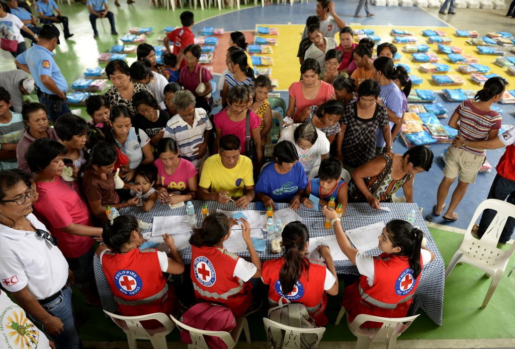 Red Cross volunteers man the table for registration of residents affected by flood caused by Typhoon Koppu that will receive food items and sleeping mats at Barangay Delfin, Albano, Isabela, north of Manila on October 20, 2015.