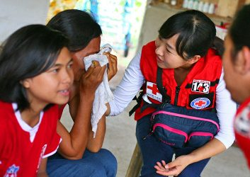 Mrs. Tapil, Eli Tambiga and Suyang Lee. 22/10/2015. Philippines, Cebu, Daanbantayan, Bateria. Mrs. Tapil in tears while speaking about her personnel story to the Red Cross personnels. Photo by Juan Carlo, Japanese Red Cross Society and Philippine Red Cross.