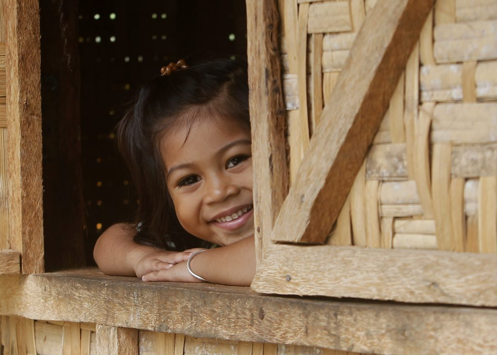 Alh Rose Pulinio, whose family is one of the beneficiary of full house, smiles as she looks out from the window of their home at Barangay Macopa in Monkayo, Compostela Valley southern Philippines November 30, 2013. One year after Typhoon Bopha locally known as Pablo destroyed houses and infrastructures and displaced thousands of residents, the IFRC and the Philippine Red Cross continue to help survivors recover with income generation projects and building of decent shelters. Photo by: Cheryl Gagalac