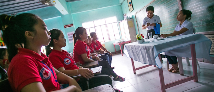 """Philippines, Leyte, Tacloban July 2015 Thanks to a Red Cross scholarship, Warren Yba""""ez, 22,  from Talisayan, Javier, Leyte, was able to quit construction work and enrol in a food and beverage class at the Asian Development Foundation College, Tacloban. Here Warren is demonstrating how to serve a restaurant customer in front of his teacher and classmates.Warren is one of 600 students from disadvantaged families being supported by IFRC as part of a Philippine Red Cross livelihoods scholarship program that will eventually see up to 1,000 young people enrolled."""