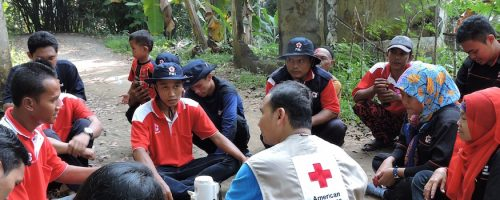 June 9, 2014. Karang Benda, Cilacap, Indonesia . Al Akbar Abubakar debriefs with Red Cross volunteers after an evacuation drill in Karang Benda village, Indonesia. The town is prone to earthquakes, tsunamis, and heavy flooding, so the American Red Cross helps families to prepare for any disasters that may come their way. The Red Cross teaches first aid, marks evacuation routes, and helps families create individualized emergency plans so they can be their own first responders if disasters strike. Local Red Cross volunteers help the town to practice emergency simulations regularly. After the simulation is finished, they talk about what went well and what could have been done better so that in a real emergency, everyone in town in prepared. Photo by Jonathan Aiken/American Red Cross