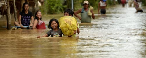 Residents of the flooded Barangay Camunatan, Isabela, evacuate to a higher ground on October 19, 2015.